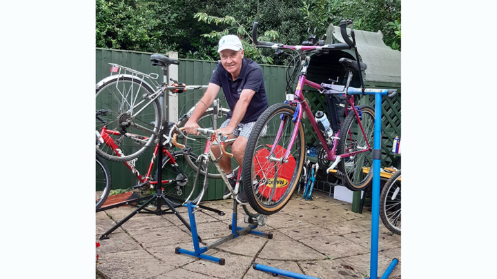 Man on a static bike smiling, surrounded by bikes